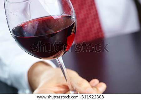 man handing glass of wine - stock photo