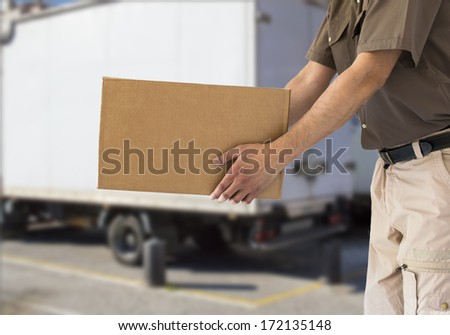 man handing out cardboard box with a truck - stock photo
