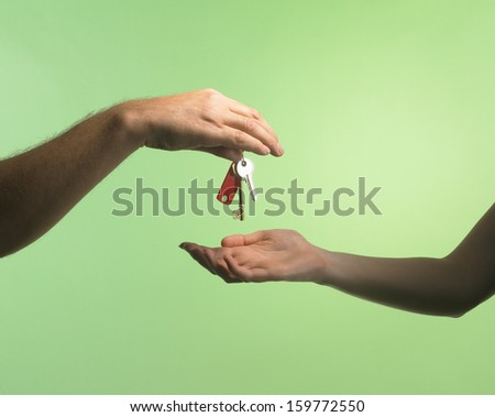 Man handing over house keys to a woman on a green background