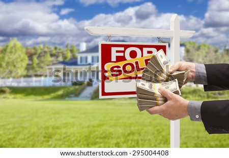 Man Handing Over Thousands of Dollars in Front of House and Sold For Sale Real Estate Sign. - stock photo
