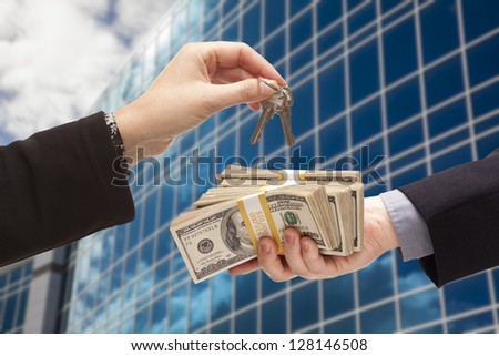 Man Handing Stack of Cash To Woman For Keys in Front of Corporate Building or Apartments. - stock photo