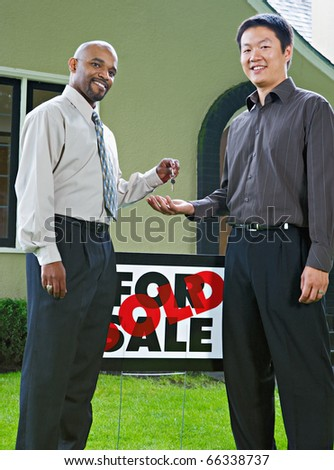 Man handing the keys to a new house to owner - stock photo
