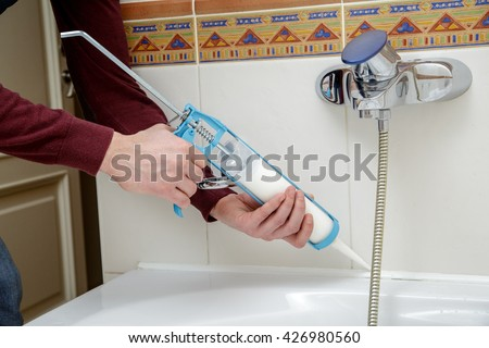 Man hands applying silicone sealant with caulking gun