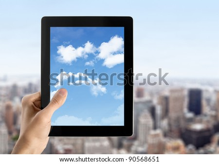 Man hands are holding contemporary digital tablet with cloudscape on screen. Concept image on cloud-computing theme. Blurred cityscape with skyscrapers on background. - stock photo
