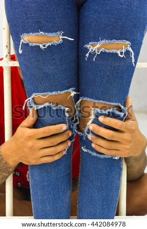 Man hands are holding the leg of his girlfriend, who wears torn jeans standing outside the prison. - stock photo