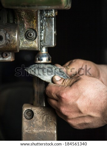 Man hands closeup working with a metal pressing machine 2