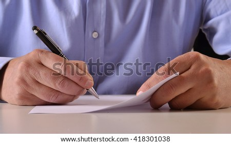 Man hands detail writing and signing a document