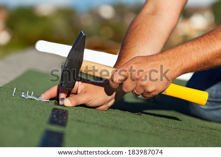 Man hands fastening bitumen roof shingles with nails and hammer - side view - stock photo