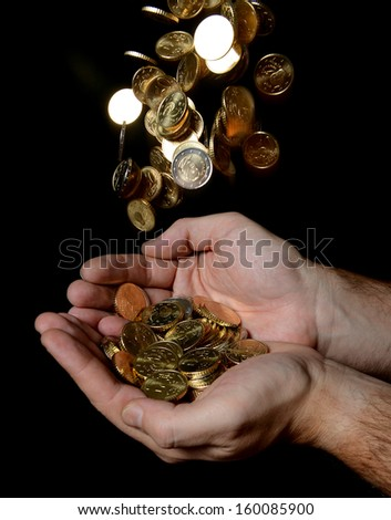 Man Hands full of money receiving a Rain of Coins isolated on black background - stock photo