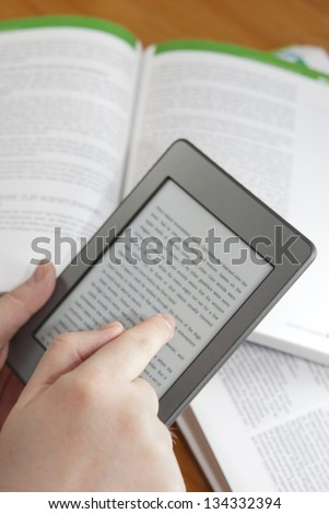 Man hands holding  an electronic book reader with text on the screen, open books in the background - stock photo