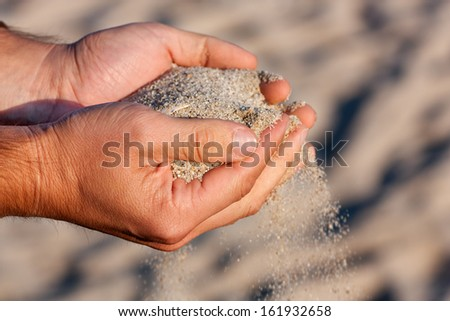 Man Hands holding and spilling sand on the beach.Very shallow depth-of-field and motion blur.