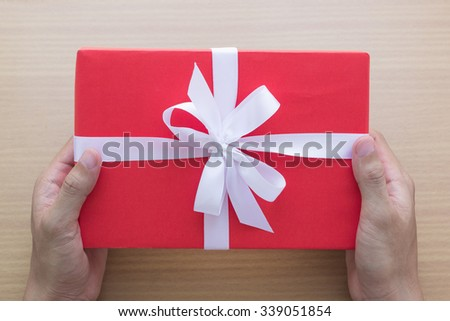 man hands holding red gift box - stock photo