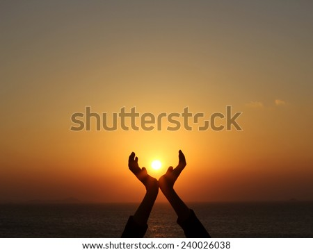 man hands holding the sun at sunrise - stock photo