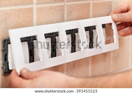 Man hands installing decorative mask onto electrical wall fixture - closeup