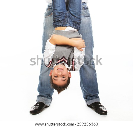 Man hands little boy headfirst isolated on white. - stock photo
