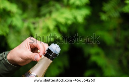 man hands open bottle of champagne alcohol and wine drink outdoor, copy space - stock photo