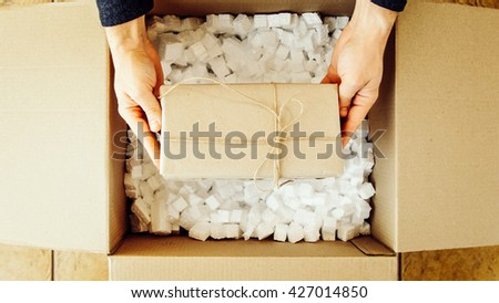 Man hands opening a parcel contains a gift. Unpacking box with another box. Surprise. Craft present box. People, delivery, shipping service, opening cardboard box or parcel at home. - stock photo