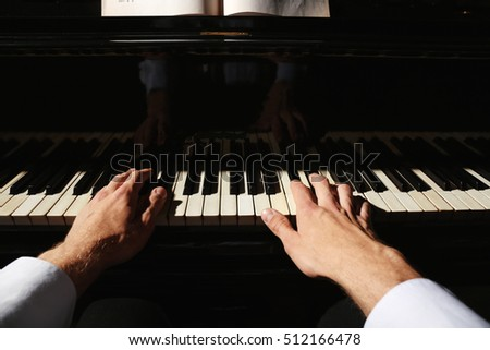 Man hands playing piano, close up