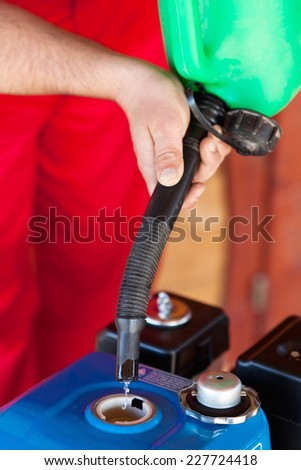 Man hands pouring gasoline into a small motor from a canister - closeup - stock photo