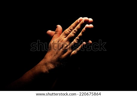 Man hands praying in dark background - stock photo