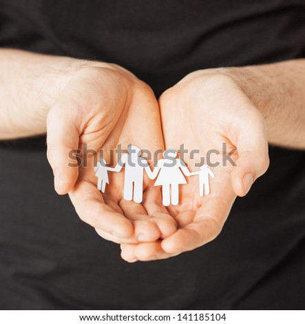 man hands showing family of paper men - stock photo