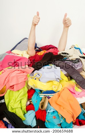 Man hands signing thumbs up reaching out from a big pile of clothes and accessories. Man buried under an untidy cluttered woman wardrobe.  - stock photo
