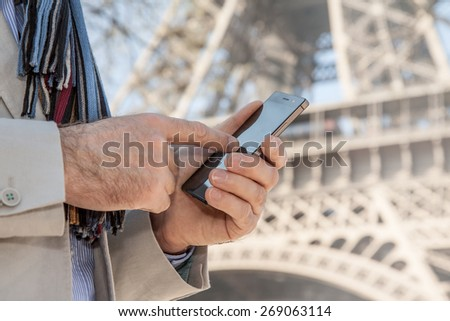 Man hands touching mobile phone screen (smartphone). Eiffel Tower as background. Tourist searching for information about Paris concept. - stock photo