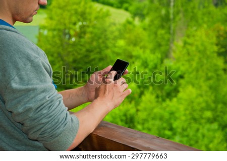 man hands touching smartphone bright background, closeup