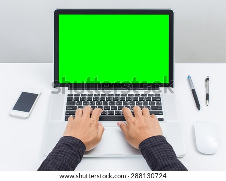 Man hands typing on green screen laptop computer - stock photo