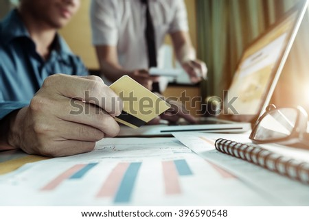 Man hands using laptop and holding credit card with digital business layers diagram as Online shopping concept  - stock photo