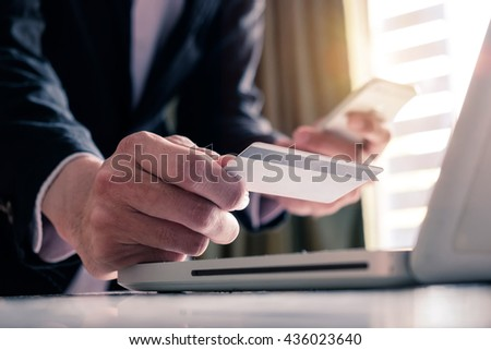 Man hands using smartphone laptop and holding credit card with social media as Online shopping concept in morning light - stock photo