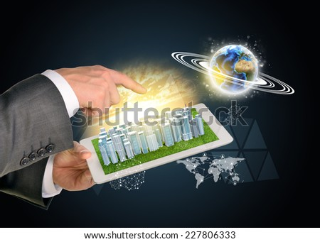 Man hands using tablet pc. Business city on touch screen. Earth near computer. Elements of tgis image furnished by NASA