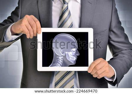 Man hands using tablet pc. Image of x-ray head on tablet screen