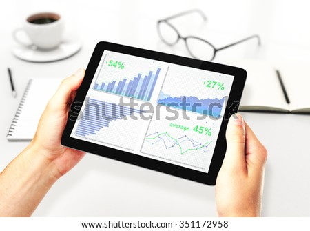 Man hands with digital tablet with business chart, coffee mug and other accessories on white table