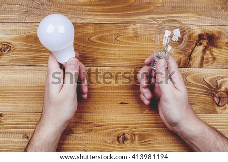 Man hands with glow-lamp and led lamp against wooden table. Man hold lamps in hands. Energy efficiency concept. - stock photo