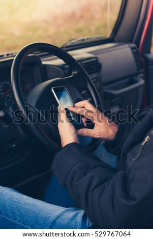 man hands with smartphone in car closeup