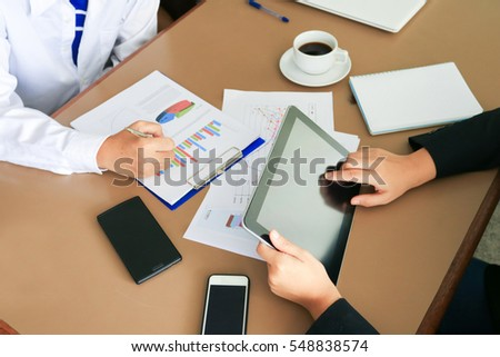 Man hands working on tablet with smartphone, coffee cup, glasses  and pen on table. vintage tone.