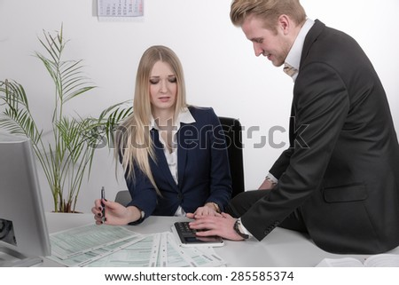 man harasses a woman at desk