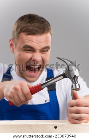 man has struck himself with hammer on finger. closeup on man shouting of pain on grey background - stock photo
