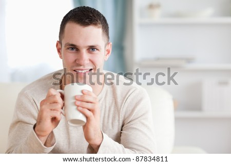 Man having a coffee in his living room - stock photo