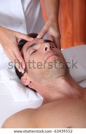 Man having a facial massage in spa center - stock photo