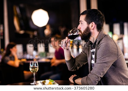 Man having a glass of wine in a bar