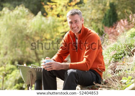 Man Having Coffee Break Whilst Working Outdoors In Garden - stock photo