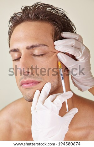 Man having crows feet removed in a beauty clinic with hyaluronic acid - stock photo