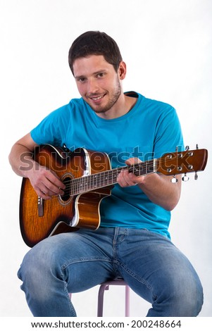 Man having fun from playing on acoustic guitar on white isolated background