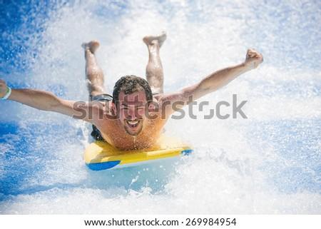 Man having fun laying on surfboard - stock photo