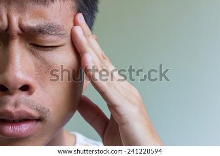 Man having headache and feeling bad, focus on finger - stock photo