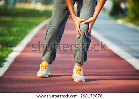 Man having pain in leg while jogging - stock photo
