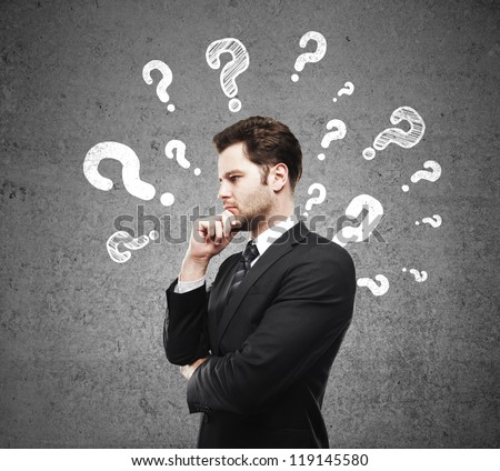 man having questions and concrete wall - stock photo