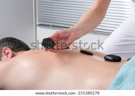 man having stone massage in spa salon. Healthy lifestyle